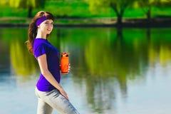 La fille dans des vêtements de sport tient une bouteille de l'eau, semblant partie et de sourire, se tenant sur la plage après sé Image stock