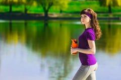 La fille dans des vêtements de sport tient une bouteille de l'eau, semblant partie et de sourire, se tenant sur la plage après sé Photographie stock libre de droits