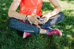 La fille dans des vêtements de sports écoutent la musique sur des écouteurs se reposant dessus Photos libres de droits