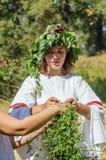 La fille dans des vêtements folkloriques russes, tisse une guirlande d'herbe et part Images libres de droits