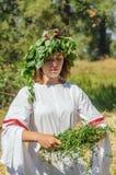 La fille dans des vêtements folkloriques russes, tisse une guirlande d'herbe et part Images stock