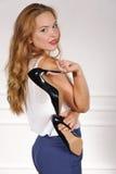 La fille dans des vêtements sport se tient dans des chaussures de chaque main images libres de droits