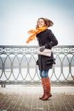 La fille dans l'écharpe rouge et le manteau noir saute près de la barrière de trellis photo libre de droits
