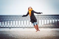 La fille dans l'écharpe rouge et le manteau noir saute près de la barrière de trellis photographie stock