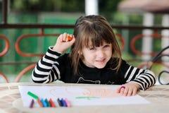 La fille dans l'équipement de Veille de la toussaint dessine le potiron Image stock