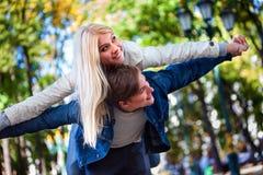 La fille dans l'amour embrasse le type pour des épaules en parc d'automne Image libre de droits