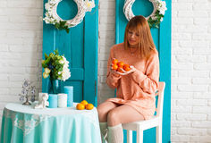 La fille dans l'intérieur avec des mandarines Images stock