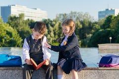 La fille dans l'uniforme scolaire empêche un garçon de lire un livre Photo libre de droits