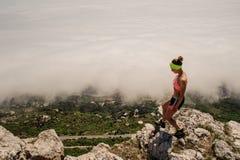 La fille dans l'uniforme, supports d'espadrilles sur une pierre regarde vers le bas la vallée dans le brouillard Images stock
