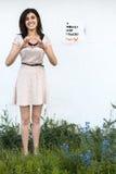La fille dans la robe blanche montre le geste de coeur Photos stock