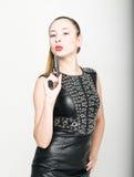 La fille dans la robe en cuir noire avec les cheveux tressés tient une arme à feu Images stock