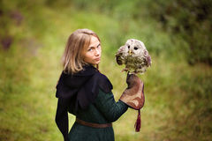 La fille dans la robe médiévale tient un hibou sur son bras photographie stock libre de droits