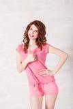 La fille dans la robe rose montre des mains de symboles photo stock