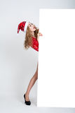 La fille dans la robe rouge dans la pleine croissance dans le chapeau de Noël tenant des bannières Image stock
