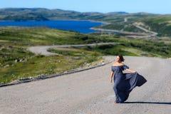 La fille dans la robe se tient sur la route Photographie stock
