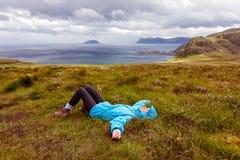 La fille dans la veste bleue se trouvant sur l'herbe sur un fond o image libre de droits
