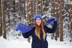 La fille dans le bleu a tricoté l'écharpe avec le chapeau dans la forêt d'hiver Image stock