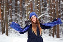 La fille dans le bleu a tricoté l'écharpe avec le chapeau dans la forêt d'hiver Images stock