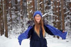 La fille dans le bleu a tricoté l'écharpe avec le chapeau dans la forêt d'hiver Photo libre de droits