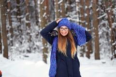 La fille dans le bleu a tricoté l'écharpe avec le chapeau dans la forêt d'hiver Photos libres de droits