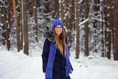 La fille dans le bleu a tricoté l'écharpe avec le chapeau dans la forêt d'hiver Photo stock