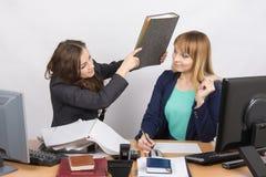 La fille dans le bureau d'un collègue qui menace de frapper son dossier Photos stock