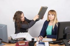 La fille dans le bureau a une tête de son grand dossier de collègue Photos stock