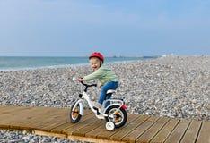 La fille dans le casque apprend monter une bicyclette à quatre roues Photographie stock libre de droits