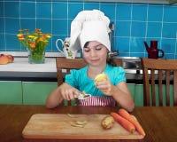 La fille dans le chapeau de chef épluche des pommes de terre Photo libre de droits