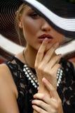 La fille dans le chapeau et le collier Photographie stock