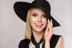La fille dans le chapeau garde la main près des sourires de rires de visage Images stock