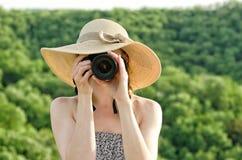 La fille dans le chapeau prend des photos dans la perspective de la forêt verte Photographie stock