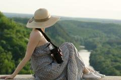La fille dans le chapeau s'assied sur la colline avec l'appareil-photo sur le fond de la forêt et de la rivière d'enroulement Photos libres de droits