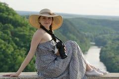 La fille dans le chapeau s'assied sur la colline avec l'appareil-photo sur le fond de la forêt et de la rivière d'enroulement Image stock