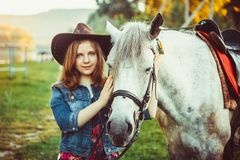 La fille dans le chapeau sur le cheval Image libre de droits