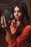 La fille dans le chemisier rouge avec le grand rouge à lèvres de yeux regarde dans le miroir qu'elle tient Photographie stock libre de droits