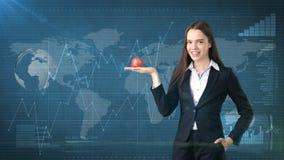 La fille dans le costume juge la pomme vibrante lumineuse disponible, symbolisant de nouvelles idées et mode de vie de concept ou Image libre de droits