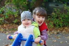 La fille dans le gilet blanc et la soeur jouent sur la motocyclette Photo libre de droits