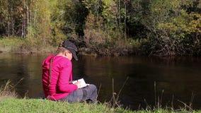 La fille dans le hoodie rose fait des notes dans un carnet se reposant par la rivière avec le bruit banque de vidéos