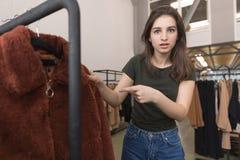 La fille dans le magasin d'habillement choisit un nouveau manteau de fourrure photos stock