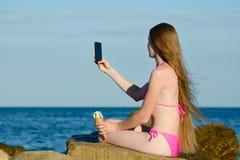 La fille dans le maillot de bain avec la crème glacée à disposition sur la plage rocheuse fait le selfie téléphoner contre la mer Images stock
