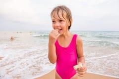 La fille dans le maillot de bain rose se tenant sur la plage et mangeant la gaufre Photo libre de droits