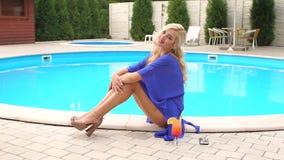 La fille dans le maillot de bain s'assied et détend près de la piscine banque de vidéos