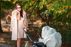 La fille dans le manteau marche avec le bébé et sourit outside Photo libre de droits