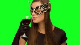 La fille dans le masque et la robe noire boivent du vin et apprécie clips vidéos