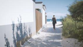 La fille dans le noir avec un sac de plage va le long du chemin vers la mer Vue du dos banque de vidéos