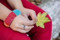 La fille dans le pantalon rouge avec le bracelet sur son poignet et le bel anneau de coeur sur son doigt tient une feuille coloré Images stock