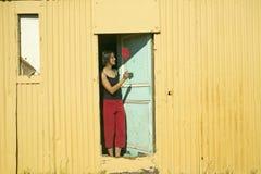 La fille dans le pantalon rouge frappe des mouches avec la tapette de mouche rouge à Cape Town, Afrique du Sud Photographie stock libre de droits