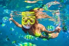 La fille dans le piqué naviguant au schnorchel de masque sous l'eau avec le récif coralien pêche Images stock