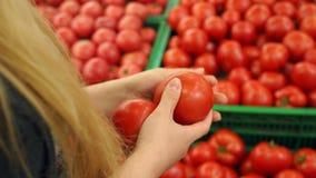 La fille dans le supermarché sélectionne des tomates, plan rapproché banque de vidéos